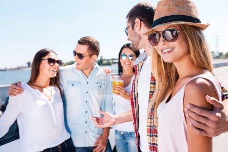 Foto de Amo a mis amigos! Grupo de jóvenes felices hablando entre sí mientras que hermosa mujer mirando a cámara y sonriendo - Imagen libre de derechos