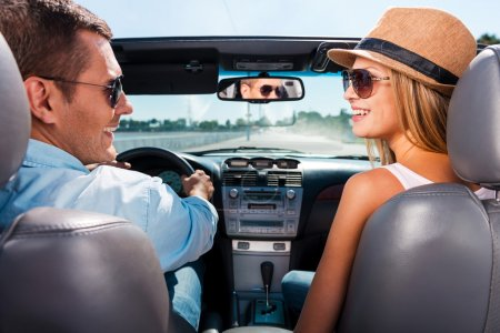 Photo for Couple in convertible. Beautiful young couple enjoying road trip in their convertible and looking at each other with smile - Royalty Free Image