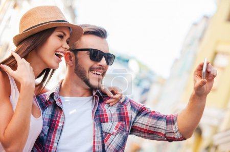 Photo for We are looking just great! Side view of happy young loving couple making selfie while standing outdoors together - Royalty Free Image