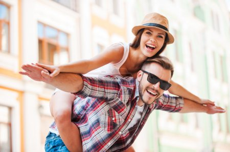 Photo pour Happy loving couple. Happy young man piggybacking his girlfriend while keeping arms outstretched - image libre de droit