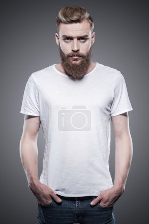 Bearded handsome man holding hands in pockets and looking at camera while standing against grey background