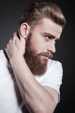 Photo for Bearded handsome. Portrait of thoughtful young bearded man touching his neck and looking away while standing against grey background - Royalty Free Image