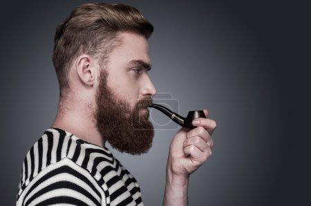 Foto de Seguros de marinero. vista lateral de seguro joven barbudo en ropa de rayas fumando una pipa y apartar la mirada mientras está parado sobre fondo gris - Imagen libre de derechos