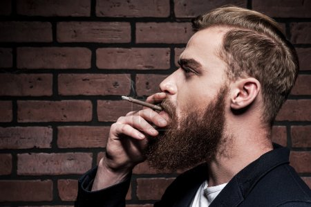 Photo for In style. Side view of handsome young bearded man smoking a cigarette while standing against brick wall - Royalty Free Image