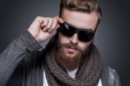 Photo for Confident in his perfect style. Portrait of handsome young bearded man adjusting his sunglasses and looking at camera while standing against grey background - Royalty Free Image