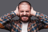 Bearded man covering ears with hands