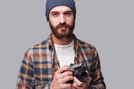 Photo for Confident photographer. Handsome young bearded man holding old-fashioned camera and looking at camera while standing against grey background - Royalty Free Image