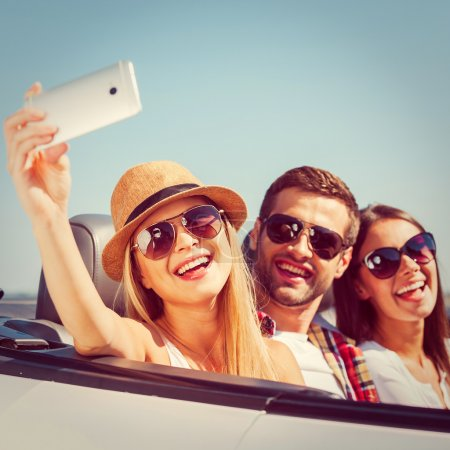Photo pour Je saisis un moment. Trois jeunes gens heureux profitant du road trip dans leur cabriolet blanc et faire du selfie - image libre de droit