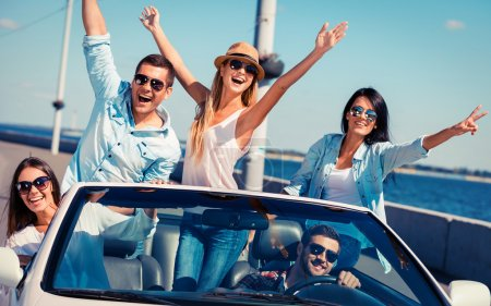 Photo for Friends in convertible. Group of young happy people enjoying road trip in their white convertible and raising their arms - Royalty Free Image