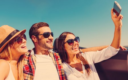 Photo for Selfie! Three young happy people enjoying road trip in convertible and making selfie - Royalty Free Image