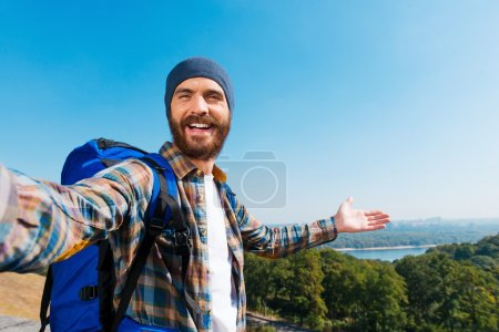 Man carrying backpack and taking a picture