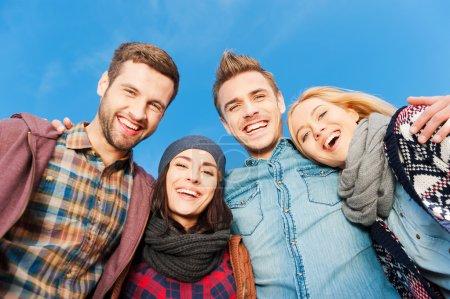 vier jugendliche gluecklich miteinander verkleben