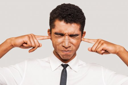 Photo pour This is too loud! Frustrated young Afro-American man in formalwear plugging ears with his fingers and keeping eyes closed while standing against grey background - image libre de droit