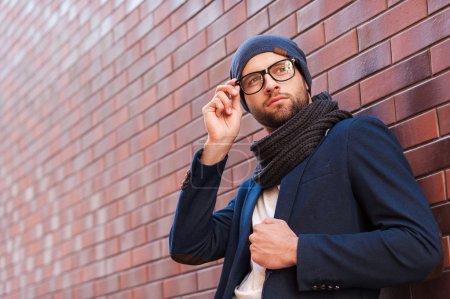 Handsome young man adjusting his eyeglasses