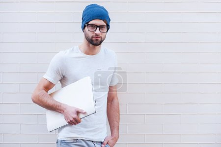 Man in eyeglasses holding laptop