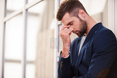 Photo for Depressed man. Frustrated young man in smart casual wear touching his face with hand and keeping eyes closed while standing indoors - Royalty Free Image
