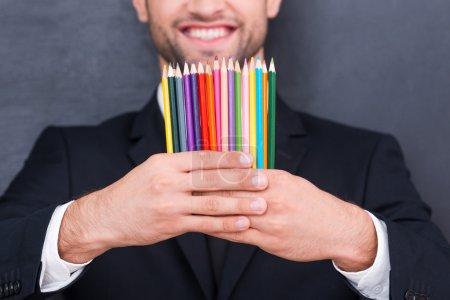 Photo pour Il a un esprit créatif. Gros plan de crayons colorés dans les mains d'un homme d'affaires souriant debout contre un tableau noir - image libre de droit