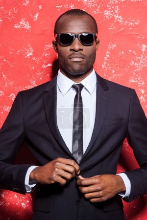 African man in formal wear and sunglasses