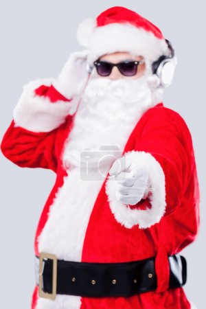 Santa Claus in sunglasses adjusting his headphones