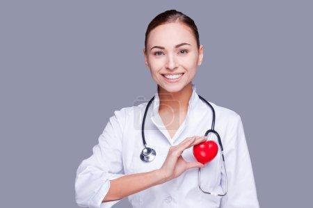 Photo pour Gardez votre cœur en bonne santé. Médecin féminin confiant en uniforme blanc tenant un accessoire cardiaque et souriant - image libre de droit