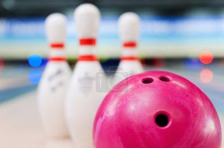 Bowling ball lying against pins