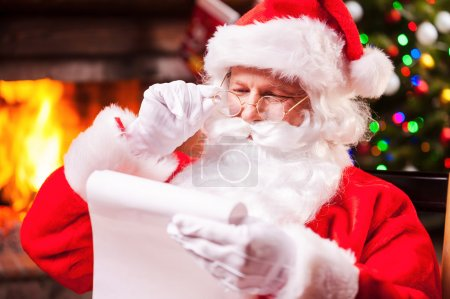 Photo for Checking his special list. Traditional Santa Claus sitting at his chair and reading a letter with fireplace and Christmas Tree in the background - Royalty Free Image