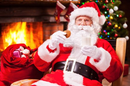 Santa Claus holding glass with milk and cookie