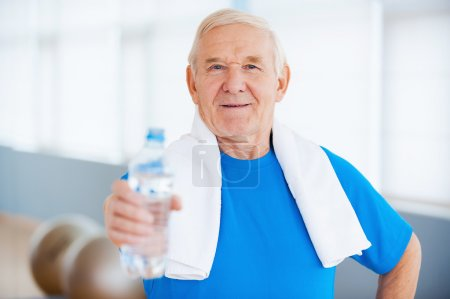 Senior man with towel and bottle with water