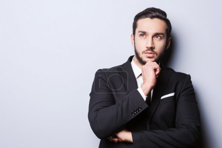 Photo pour Thoughtful young man in formalwear holding hand on chin and looking away while standing against grey background - image libre de droit