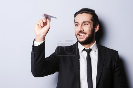 Photo for Businessman with paper airplane. Playful young man in formalwear holding paper airplane and smiling while standing against grey background - Royalty Free Image