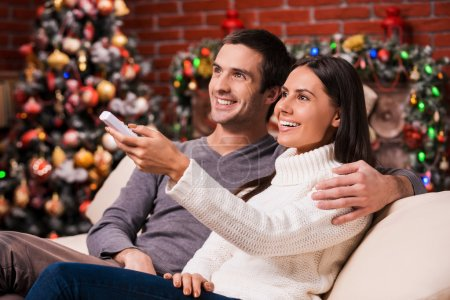Photo pour Side view of beautiful young loving couple bonding to each other and smiling while watching TV together with Christmas Tree in the background - image libre de droit