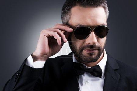 Mature man adjusting his sunglasses