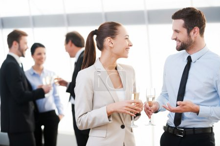 Photo for Two cheerful business people drinking champagne and talking while other people communicating in the background - Royalty Free Image