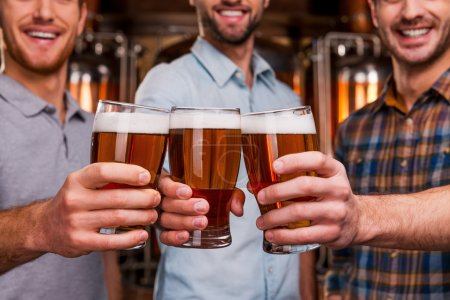 Young men stretching out glasses with beer