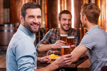 Photo for Handsome young man toasting with beer and smiling while sitting with his friends in beer pub - Royalty Free Image
