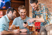 Men drinking beer in pub with smart phone