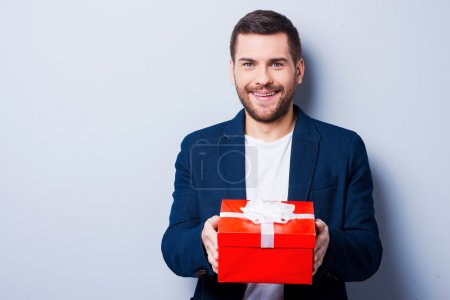 Photo for Handsome young man in formalwear giving a gift to you while standing against grey background - Royalty Free Image