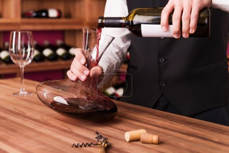 Sommelier pouring wine to decanter