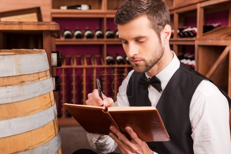 Sommelier writing in note pad