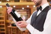 Man examining wine bottle