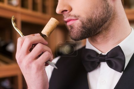 Man smelling wine cork