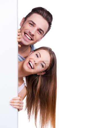 Loving couple peeking out copy space