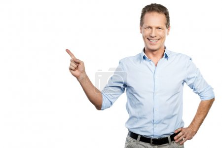 Foto de Happy mature man in shirt looking at camera and pointing away while standing against white background - Imagen libre de derechos