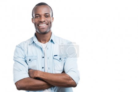 Foto de Handsome young black man keeping arms crossed and smiling at camera while standing against white background - Imagen libre de derechos