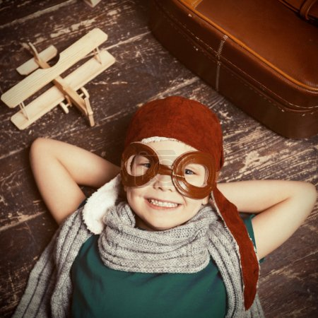 Photo for Top view of happy little boy in pilot headwear and eyeglasses lying on the hardwood floor and smiling - Royalty Free Image