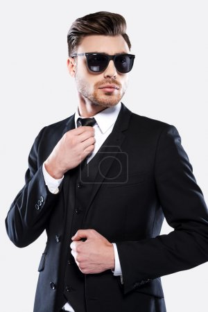 Photo for Portrait of handsome young man in formal wear and sunglasses adjusting his necktie and looking at camera - Royalty Free Image