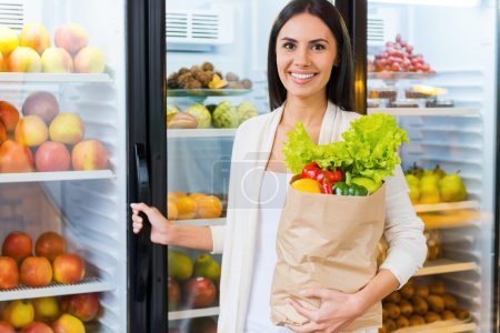 Photo for Beautiful young woman holding shopping bag with food and smiling while standing in grocery store near refrigerator - Royalty Free Image