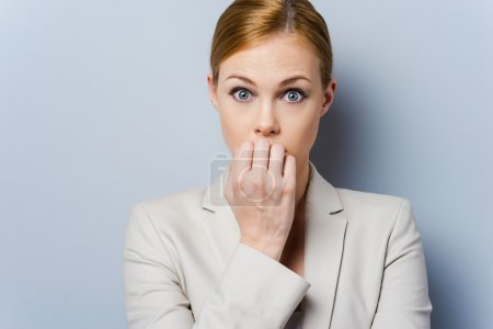 Nervous businesswoman biting nails