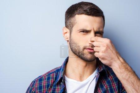 Photo pour Portrait de jeune homme frustré en chemise décontractée tenant le nez et exprimant la négativité - image libre de droit