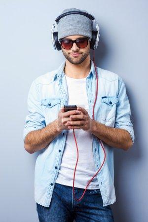Stylish man in headphones holding MP3